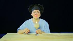 黑背景的妇女厨师品尝果子圆滑的人并且显示标志OK 股票录像