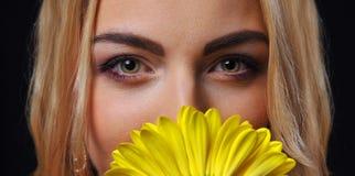 黑背景的金发女孩妇女与黄色菊花花束分支在手上 免版税库存照片