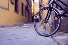 黑自行车的轮子在墙壁附近的停车处 免版税库存图片