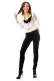 黑色严密的牛仔裤的可爱的微笑的女孩 免版税库存图片