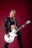 黑色吉他皮革摆在的岩石丝毫妇女 免版税库存照片