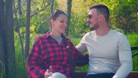 黑色和红色衬衣的一个女孩坐长凳,一件灰色T恤杉的人坐下给女孩 股票录像