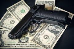 黑色和镀铬物开枪手枪和金钱美元背景 免版税图库摄影