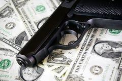 黑色和镀铬物开枪手枪和金钱被过滤的美元背景 免版税库存照片