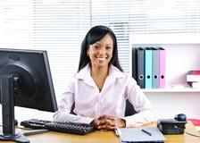 黑色女实业家服务台微笑 免版税库存图片