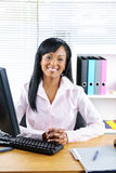 黑色女实业家服务台微笑 库存图片
