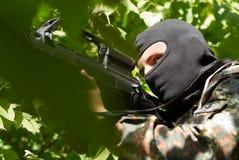 黑色屏蔽的恐怖分子与枪 免版税库存图片