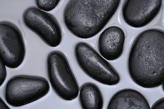 黑色岩石在水中 库存图片