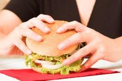黑色拿着汉堡包的加工好的妇女 免版税库存图片