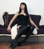 黑色束腰的妇女坐沙发 免版税库存图片