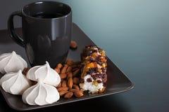 黑色杯用蛋白甜饼、杏仁和蛋白软糖 免版税库存图片