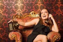 黑色椅子礼服坐的葡萄酒妇女 库存照片