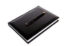 黑色物质笔记本笔 免版税库存图片