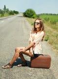 黑色玻璃的女孩坐手提箱 免版税库存照片