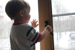 黑色白色 孩子在窗口基石站立并且尝试 库存照片