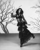 黑色的一个外籍人女孩,透明,摆在反对一个阴沉的森林的背景的葡萄酒礼服,被创造  库存照片