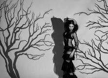 黑色的一个外籍人女孩,透明,摆在反对一个阴沉的森林的背景的葡萄酒礼服,被创造  图库摄影