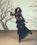 黑色的一个外籍人女孩,透明,摆在反对一个阴沉的森林的背景的葡萄酒礼服,被创造  库存图片