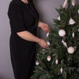 黑色的一名妇女装饰一棵圣诞树 免版税库存图片