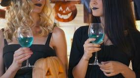 黑色的两名妇女喝蓝色鸡尾酒的在传统万圣夜党 股票录像