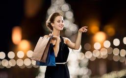 黑色的妇女与在圣诞节的购物袋 免版税库存照片