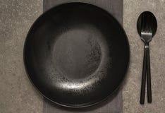 黑色的盘子、利器和餐巾在灰色石桌上 库存照片