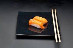 黑色的盘子用三文鱼寿司和筷子 库存图片