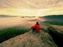 黑色的远足者在岩石峰顶 在山的美妙的破晓,在深谷的重的橙色薄雾 免版税库存照片