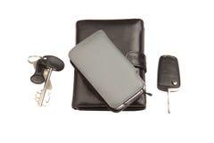 黑色皮革钱包、电话和关键字 免版税库存照片