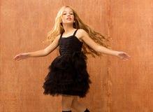 黑色礼服孩子女孩跳舞和扭转葡萄酒 库存照片