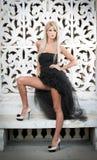 黑色礼服摆在的美丽的妇女室外 免版税库存照片