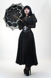 黑色礼服的哥特式吸血鬼与伞 免版税库存图片