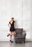 黑色礼服的美丽的白肤金发的女孩在扶手椅子附近 库存照片