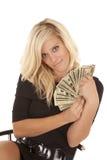 黑色礼服货币坐微笑妇女 免版税库存图片