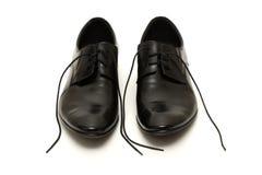 黑色经典之作系带被解开的人s鞋子 库存照片