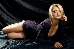 黑色缎织品的金发碧眼的女人 图库摄影