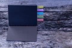 黑色色的日志选项 与笔记的五张五颜六色的书签 免版税库存照片