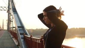 穿着黑色衣服准备训练的运动女孩 黎明时将头发绑在马尾上的跑步者 太阳射线 股票录像