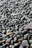 黑色被舍入的石头 库存照片