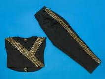 黑色裤子和女衬衫有发光的结束的在蓝色背景 r 库存照片