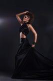 黑色长的礼服的妇女在黑暗的背景 库存图片