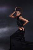 黑色长的礼服的妇女在黑暗的背景 图库摄影