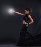 黑色长的礼服的妇女在黑暗的背景 免版税库存图片