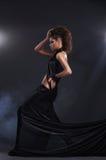 黑色长的礼服的妇女在黑暗的背景 库存照片