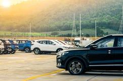 黑色,白色和蓝色新的汽车在具体停车场停放了在工厂在山附近 售车行概念 汽车股票 免版税库存图片