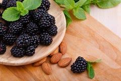 黑莓特写镜头在一块棕色板材的在木背景 杏仁和薄菏在成熟莓果附近 滋补食物 免版税库存照片