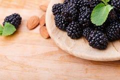 黑莓特写镜头在一块棕色板材的在木背景 杏仁和薄菏在成熟莓果附近 滋补食物 库存图片