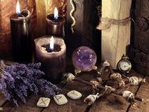 黑蜡烛、五角星形、诗歌和淡紫色花与水晶球 免版税库存照片