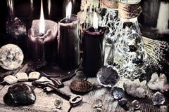 黑蜡烛、水晶和石头、古老诗歌、钥匙和仪式瓶在巫婆桌上 库存照片