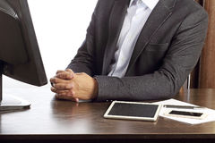 黑衣服的人在白色背景隔绝的他的书桌 图库摄影